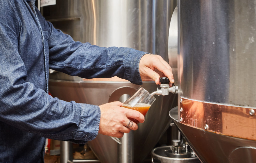 brewer pouring glass of craft beer in Peter B's Brewpub
