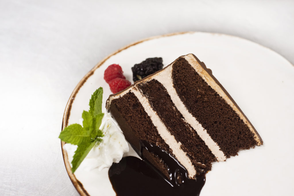 Chocolate cake garnished with whipped cream berries and chocolate sauce